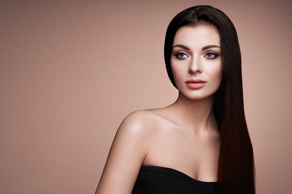 Beautiful Ukrainian woman with long smooth hair posing in a dainty black dress